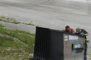 two men go dumpster diving in the middle of the day