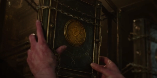 Gnarled hands of Doctor Strange reach for the book of Cagliostro